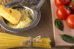 Pasta, tomatoes, basil and grated cheese. - stock photo
