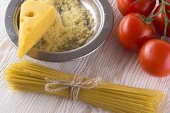 Pasta, tomatoes and grated cheese. Stock Photos