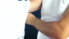 Footballer putting on a white T-shirt on black background Stock Footage