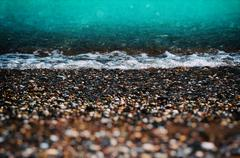 Aqua tidal beach pebble shingle vintage film composition Stock Photos