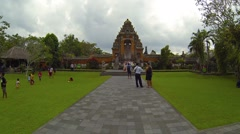 Children play soccer on the greens in front of Taman Ayun Royal Temple in Bal Stock Footage