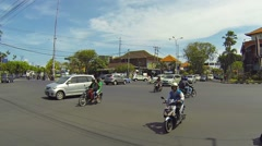 Motorcycle ignores traffic lights to cross busy stream of traffic in Bali Stock Footage