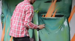 The artist draws graffiti on a fence. Stock Footage