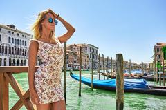 Beautiful Girl Is Standing By the River in Venice near the gondola, Italy - stock photo