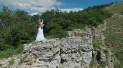 bride and groom kissing on the rock. - stock footage
