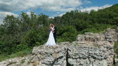 bride and groom standing on the rock. - stock footage