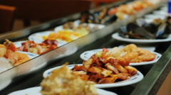 Bar with seafood. Plates of food moving through the pipeline Stock Footage