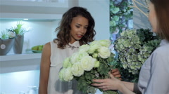 Female buyer examines the bouquet of roses Stock Footage