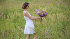 Summer flowering field and a beautiful girl in a white sundress Stock Footage