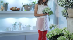 Woman chooses bouquets of flowers at flower shop - stock footage
