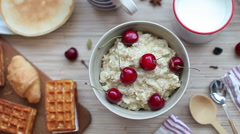 Breakfast of Porridge With Cherries and Pastry Stock Footage