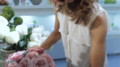 Woman takes a bouquet of pink roses at flower shop Stock Footage