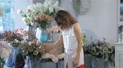 Woman picks one rose from the vase at flower shop - stock footage
