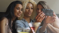4K Young women relaxing in a bar with cocktails & taking selfie with cameraphone Stock Footage