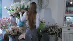 Female florist inspecting flowers at her flower shop - stock footage