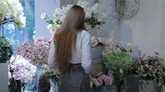 Female florist rearranges flowers at flower shop Stock Footage