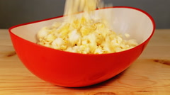 Popcorn is falling down into a red bowl. Getting ready before watching movies Stock Footage
