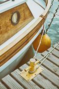 Wooden yacht moored to bollard in marina. Stock Photos