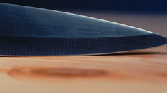 Stainless blade of a sharp kitchen knife is slipping on the wooden cutting bo Stock Footage