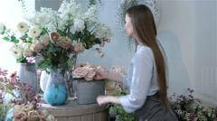 Female florist moving flowers near the window at flower shop Stock Footage