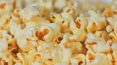 Close-up of popcorn background and a hand picks one piece of popcorn Stock Footage