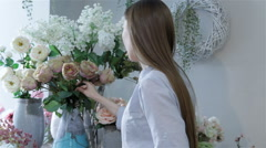 Female florist arranges flowers in vases at flower shop Stock Footage
