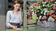 Female florist accepts order for bouquet of flowers at flower shop Stock Footage