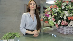 Female florist leans on her working desk - stock footage