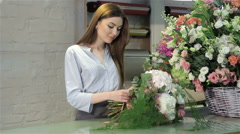 Female florist demonstrate a bouquet of white flowers at flower shop - stock footage