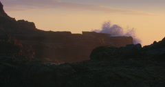 Waves crashing rocky shoreline as sun is setting on piha beach, auckland, New Stock Footage