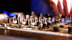 Hands of DJ tweak various track controls on DJ mixer console at nightclub Stock Footage