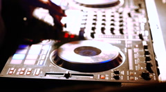Hands of DJ tweak various track controls on DJ mixer console at nightclub - stock footage