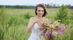Happy young girl with a bouquet of wild flowers in his hand Stock Footage