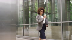 Afro American businesswoman in city using smart phone with takeaway coffee Stock Footage