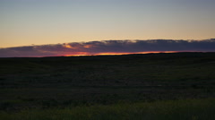 Time lapse - sunrise behind clouds over green grass of prairie valley Stock Footage