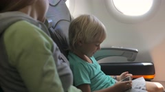 Child playing games on smartphone, smiling with mother traveling by plane - stock footage