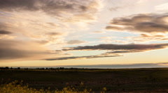Time lapse - Clouds race to horizon over prairie valley and grasses Stock Footage