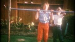 3476 children do pullups on the backyard high bar-vintage film home movie Stock Footage