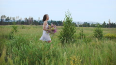 Beautiful inspired woman talking on a blossoming field with a bouquet of Stock Footage