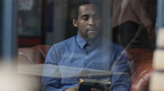 4K Pensive man sitting alone in cafe, looking out of window & using tablet Stock Footage
