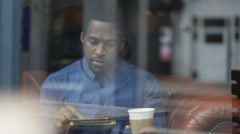 4K Portrait man sitting alone in cafe, using computer tablet & smiling to camera - stock footage