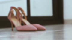 Pair of classical pink-beige woman wedding shoes on the floor - Changing defo Stock Footage