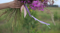 Beautiful inspired woman holds a bouquet of wildflowers Stock Footage