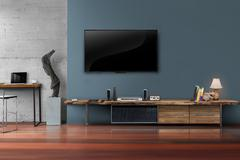 Led tv on dark blue wall with wooden table in living room - stock photo