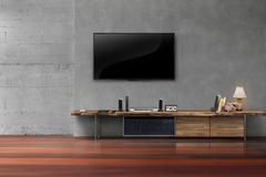 Living room led tvs on concrete wall with wooden table media furniture Stock Photos