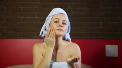 Woman dressed in a bath towel spreads face cream. Skin care. daily facials skin Stock Footage