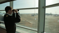 In airport air traffic controller is looking into distance using the binoculars Stock Footage