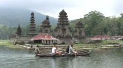 Traditional dugout canoe (Pedau) in Tamblingan lake with Komala Tirta temple Stock Footage