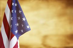 American flag in front of brown background. Advertising space - stock photo