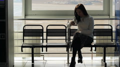 The woman is sitting in airport waiting hall waiting for someone Stock Footage
